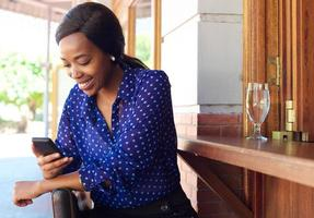 Smiling business woman reading text message on cell phone