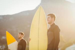 Two men in wetsuits with a surfboard