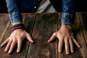 Beautiful men hands on table, jeans casual shirt, tattoo, wrist photo