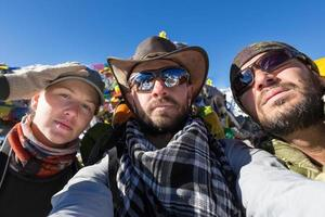 Three tourists two men woman selfie.