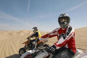 hombre montando en quad en el desierto