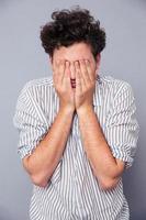 Mann bedeckt sein Gesicht mit Handflächen
