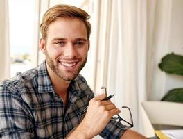 Young caucasian entrepreneur smiling at camera with glasses photo