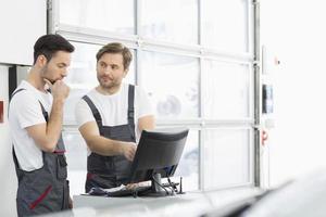 mannelijke automonteurs converseren in reparatiewerkplaats