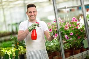 happy florest watering flower in glasshouse