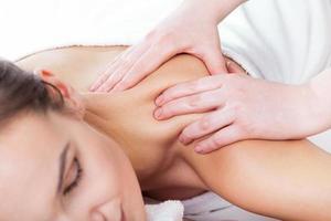 Hands massaging female neck photo