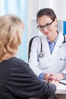 Doctor comforting female patient photo
