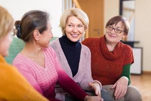 Smiling female pensioners on sofa