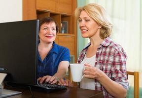 dos mujeres maduras navegando por la web