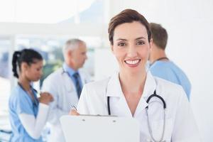 Confident female doctor holding clipboard photo