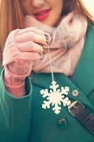 jovem fêmea segurando a decoração de floco de neve