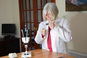 cientista feminina sorrindo para uma rocha