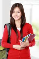 Beautiful female student with books smiling