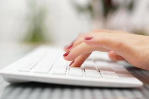 dedos femeninos escribiendo en el teclado blanco