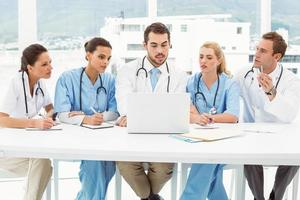 Male and female doctors using laptop photo