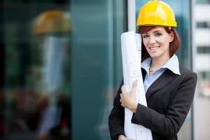 glimlachende vrouwelijke consulent naast een glazen gebouw