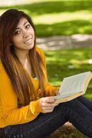 Estudiante relajado leyendo el libro en el parque foto