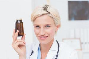 Confident female doctor holding medicine bottle