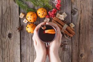 Female hold glass of hot mulled wine