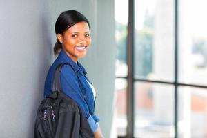 african female student leaning against a wall