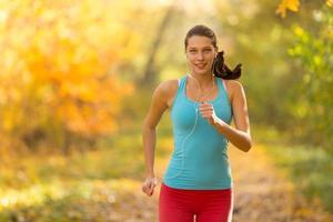 Modelo de fitness femenino entrenando afuera y corriendo