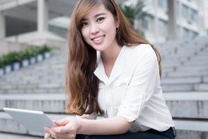 Estudiante asiática con tableta en el campus foto