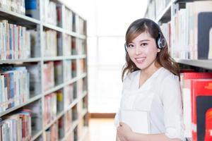 Portrait de belle étudiante asiatique dans la bibliothèque
