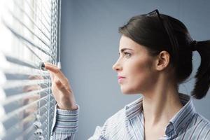mujer atractiva mirando a través de las persianas foto