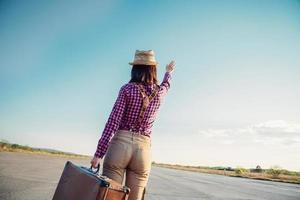 mujer con maleta agita su mano foto