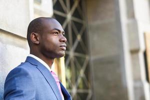 Handsome black man wearing suit in urban background photo