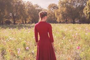 mujer joven en pradera al atardecer foto