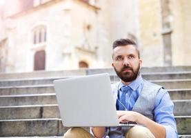 Hipster businessman with laptop photo