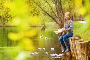 Girl near pond playing with paper boats in forest