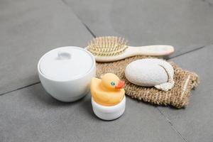 bienestar, pato de goma, cepillo para el cabello, guante, piedra pómez y tazón