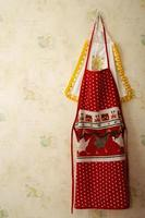 Red kitchen apron hanging up on a wall