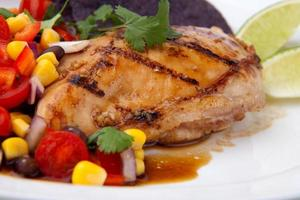 Grilled chicken breast with tomato and corn garnish