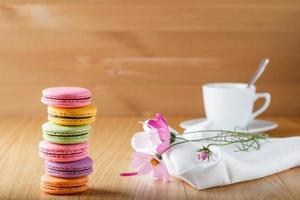 Six colorful french macaron and cup