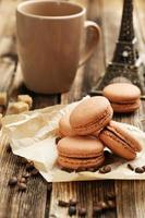 Coffee macarons with coffee beans on brown wooden background photo