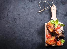 Chicken drumsticks on wooden board