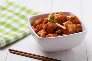 trozos de pollo frito rebozados con salsa agridulce foto
