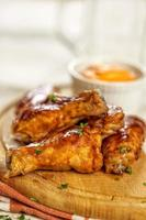 Buffalo chicken wings on wooden plate with bbq sauce