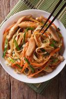 Chow mein with chicken and vegetables, top view vertical photo