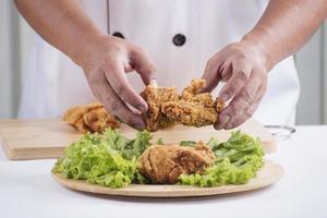 cook preparing fried chicken