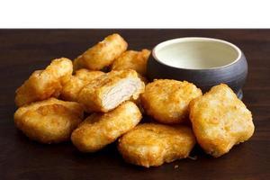 Nuggets de pollo rebozado frito dorado. foto