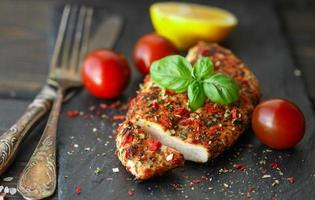 Chicken fillet with tomato and Basil on black plate