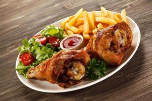 Roasted chicken drumsticks, French fries and vegetables