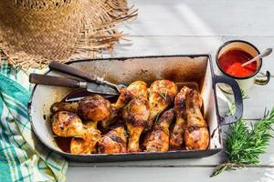 Hot chicken legs with herbs and sauce in rustic kitchen