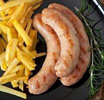 Chicken sausages grilled with a side dish of french fries