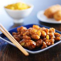 orange chicken on blue plate photo