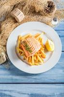 Tasty salmon with chips served on plate with lemon